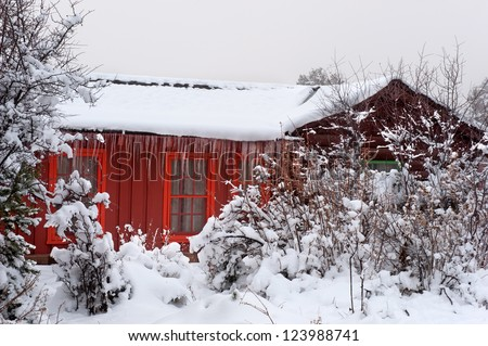 A red, frozen cabin in the forest nestled in a snowy setting with ice cycles hanging off the roof.