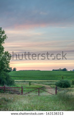 A red gate leads into a lush meadow. - Shutterstock ID 163138313