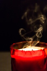 A red glass container with a candle that has been blown out showing smoke trails to the right of the frame. Left side has room for text.