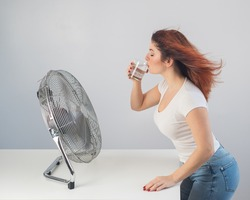 A red-haired Caucasian woman chills by the electric fan and drinks a cold drink. Climate control in the apartment