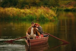 A red-haired girl in a checked jacket and red trousers leaned her head on the shoulder of a bearded guy in a coat, sitting in a red wooden boat with oars on the lake against a background of reeds.