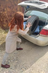 a red-haired girl in a coat loads a dirty tire into the trunk of a car