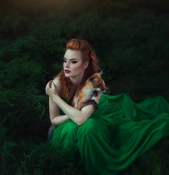 A red-haired girl in a green dress is sitting with a fox in a fairy forest. Beautiful young woman with a young fox. Creative colors and Artistic processing.