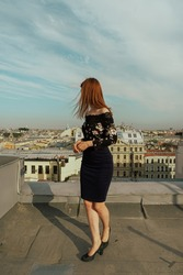a red-haired girl walks on the roofs of St. Petersburg on the background of the Iskakevsky Cathedral