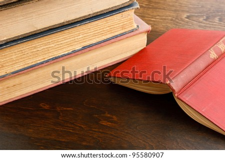 A red hardcover book lies open on a dark wood table with old weathered books in the background