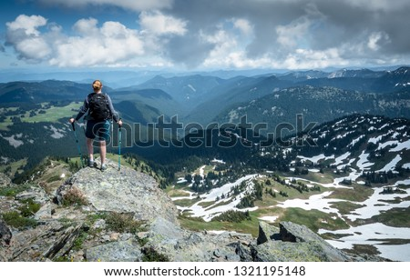 A red headed female hiker stands at Fremont Lookout and surveys the forest covered rolling mountains of Mount Rainer National Park, Washington State, USA.