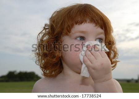 A red headed toddler girl blowing her nose.