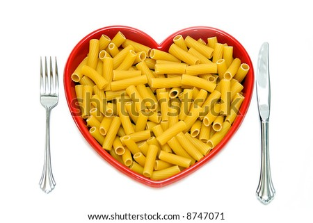 A red heart dish filled with rigatoni pasta - knife, fork on white background.