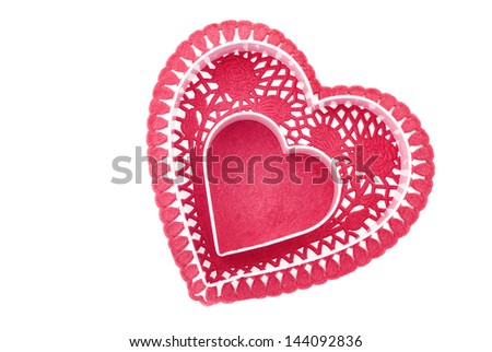 A red heart doily with pink cookie cutter hearts, isolated on a white background
