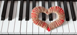 a red heart lies on the black and white piano keys