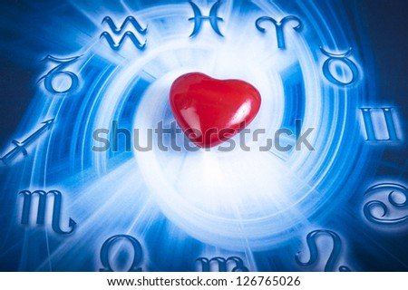 a red heart over blue zodiac background