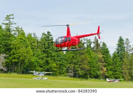 a red helicopter and green forest