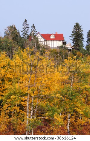 A red house in autumn forest at the north Saskatchewan river valley, Edmonton, Alberta, Canada
