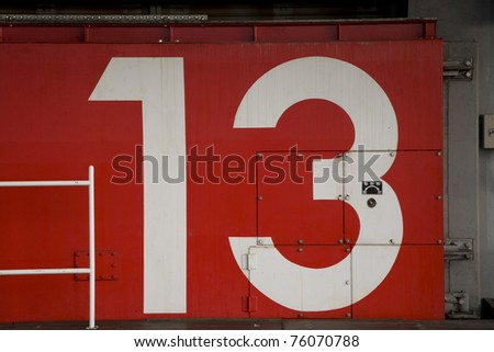 a red japanese tsunami watertight door in osaka bay area with the number 13 painted on it
