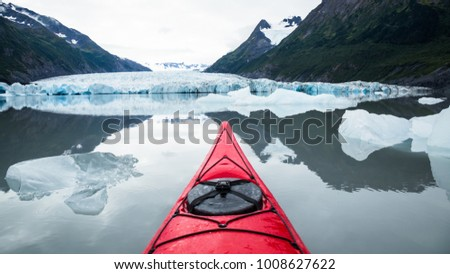 A red kayak floats among many icebergs calved from the Spencer Glacier in the distance. Nearly perfect calm water of an alpine lake in Alaska.
