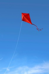 A red kite flying against a vivid blue sky