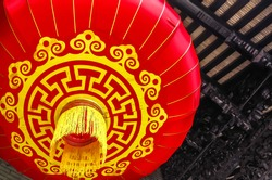 A red latern hang on the traditional Chinese building