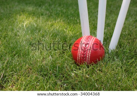 A red leather cricket ball lying in green grass at the base of three white wooden cricket stumps. Set on a landscape format. - stock photo
