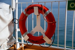 A red lifebuoy hangs on the rail of a boat on the open sea - ready to help people in distress - in the background you can see the deep blue sea on a beautiful summer day - concept of rescue