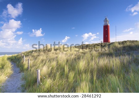 a red lighthouse at the beach in the dunes with a blue sky