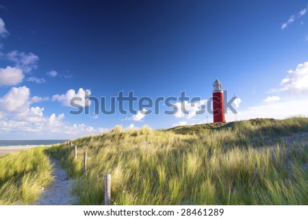 a red lighthouse at the beach in the dunes with a blue sky in summer