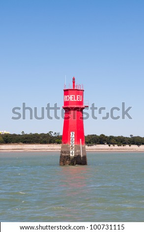 A red lighthouse in the middle of the ocean at La Rochelle, France