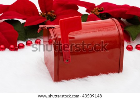 A red mailbox with poinsettia flowers on a white background