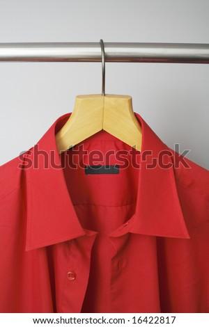A Red men's dress shirt hanging on a hanger