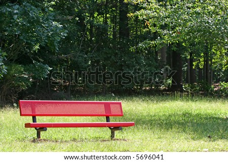 A red metal bench in  a public park