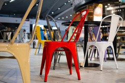 A red metal chair among the colored chairs in an empty airport food court. Coronavirus and tourism.