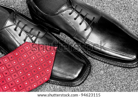 A red necktie on a new pair of black leather dress shoes