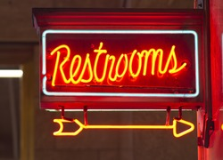 A red neon sign points the way to the restrooms in Union Station
