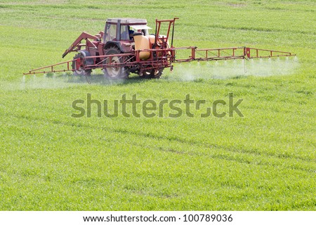 A red old tractor fertilizes a green field in spring