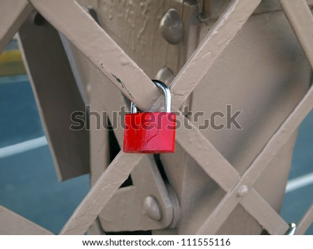 A red padlock with a heart carved into it, locked to a section of the Brooklyn Bridge.
