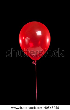 A red party balloon on a black background