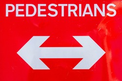 A red pedestrians sign with a doubleheaded arrow pointing in both directions