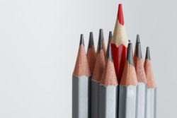 A red pencil standing out from the crowd of many identical gray brothers on a white background. Leadership, uniqueness, independence, initiative, strategy, dissent, think differently