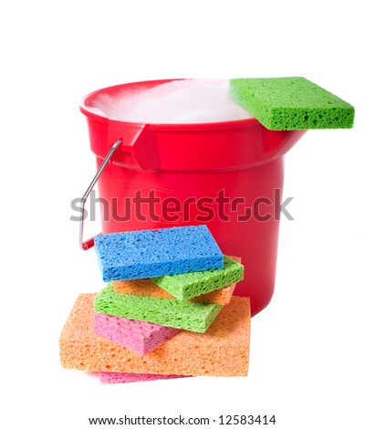 A red plastic bucket on a white background with several brightly colored sponges.  Cleaning theme