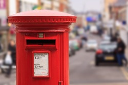A red post box set against a de-focused city centre background