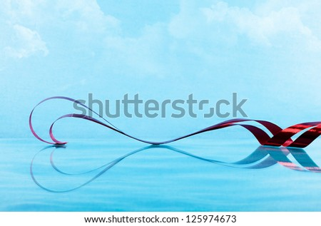 a red ribbon and its reflection on the water forming a heart shape with blue sky and clouds on background - stock photo