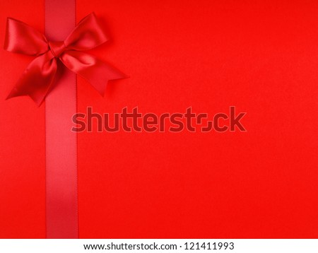 A red ribbon bows on bright red  background
