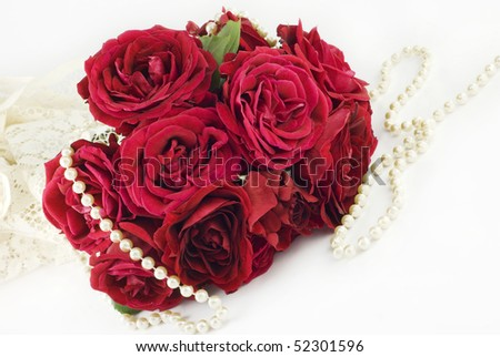 A red rose bouquet with lace and pearls on a horizontal background, perfect for Valentine's Day