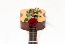 A red rose on a classical guitar. Happy valentine's day greeting with place for text copy space. A romantic gift. Music lessons. Serenade for love.