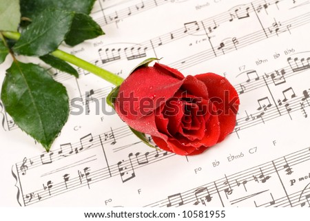 A red rose rests atop a sheet of piano music during a wedding reception