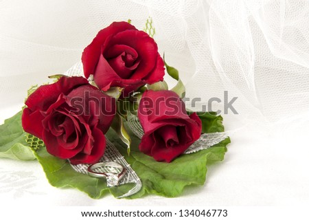 a  red roses and wedding rings on white background #134046773