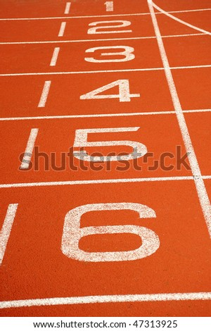 A red running track with lane numbers painted upwards