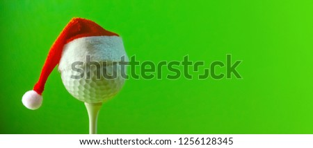 A red Santa Claus hat is worn on a golf ball mounted on a tee. A long banner with copy space on the subject of golf at Christmas and in the new year. Saturated green background. #1256128345