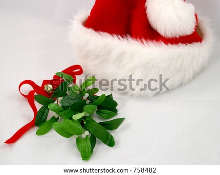 A red santa claus hat with a sprig of mistletoe.