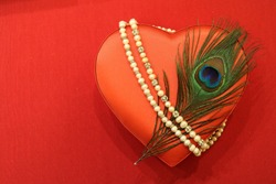 A red satin heart with a peacock feather is tied with a pearl necklace on a red on a red background in the right half of the photo.