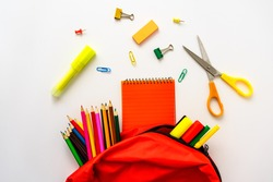 A red school bag with colored pencils, highlighter, notepad and scissors scattered on a white background. Flat lay, back to school.